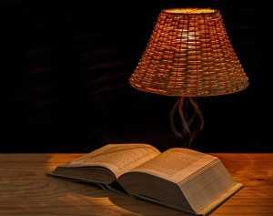 Book open on a table with a lamp beside it