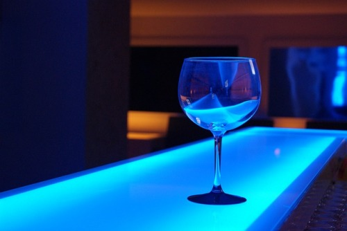 A wine glass on a bar surface in a disco