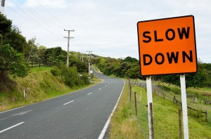 "Road sign that says ""Slow down"""